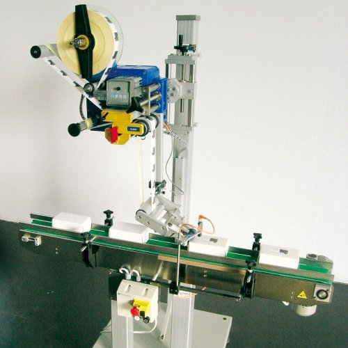 Top labelling machine for the application of labels on the top side